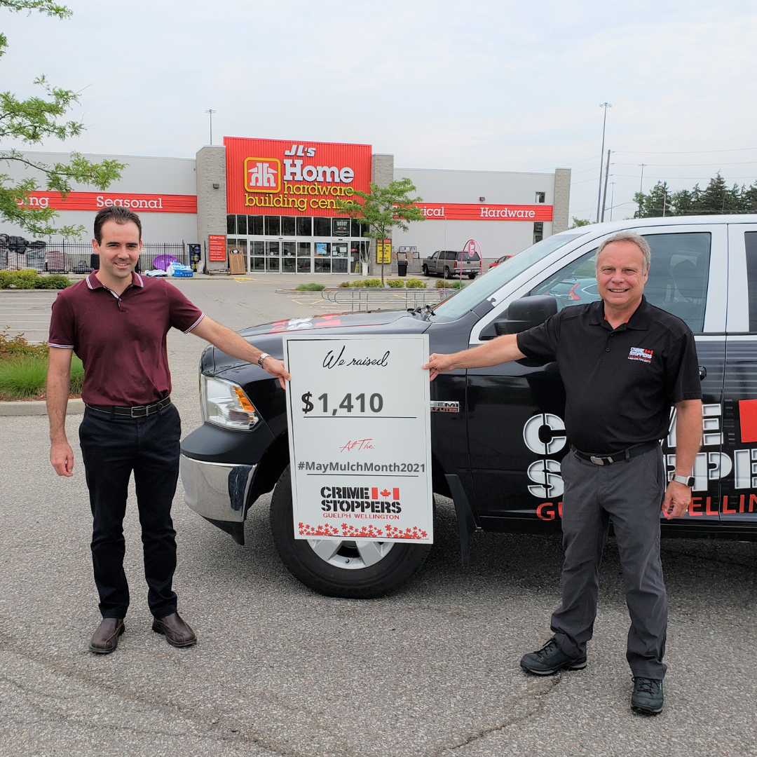 Andre of JL's Home Hardware and CSGW Vice Chair Dave stand in front of the CSGW truck with the Home Hardware store in the background. They hold a board that bears the amount raised in the May fundraiser - $1,410.