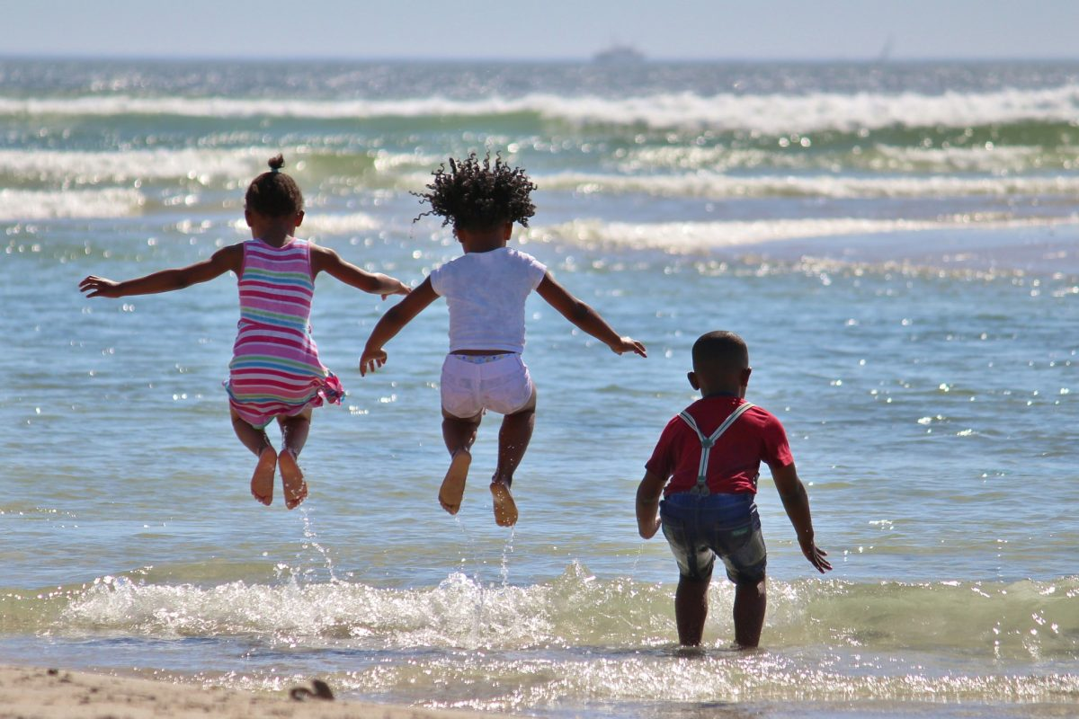 Three children frolic in the waves on the beach